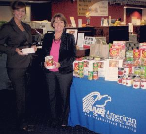 Amy Engelberg, EVP/Chief Lending Officer and Angie Sherlock, SVP/Chief Compliance Officer stand next to the food items generously donated during our Thanksgiving Food Drive benefiting Sheridan House.